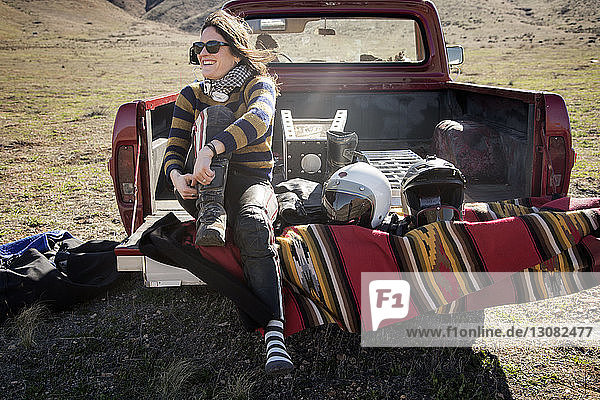 Happy female biker sitting on pick-up truck at countryside