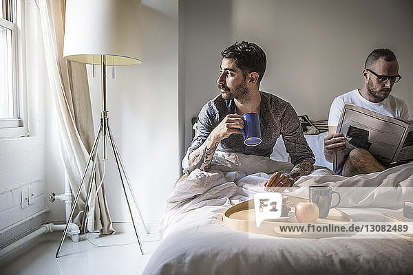 Gay man having breakfast while partner reading newspaper on bed at home