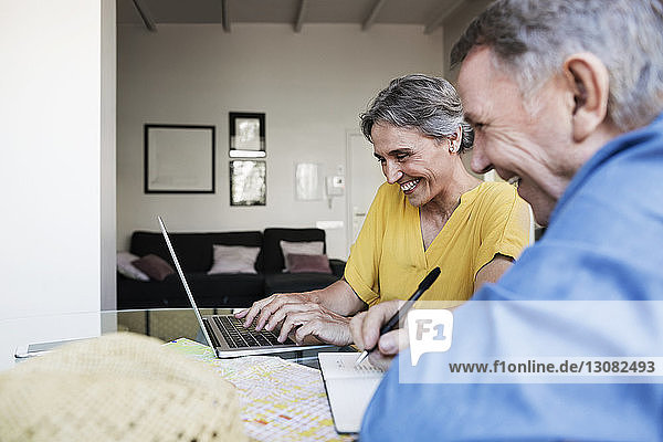 Cheerful senior couple using laptop while planning vacation at home