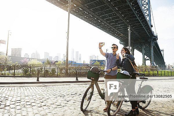Pärchen  das sich im Stehen mit Fahrrädern gegen die Manhattan-Brücke stellt