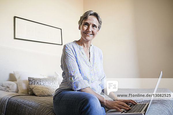 Portrait of happy mature woman sitting with laptop on bed