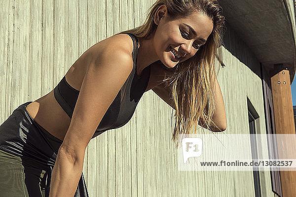 Lächelnde junge Frau schaut nach unten  während sie sich an einem sonnigen Tag in der Stadt gegen eine Wand beugt