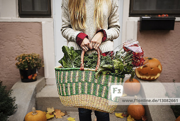 Midsection of woman holding shopping bag with food
