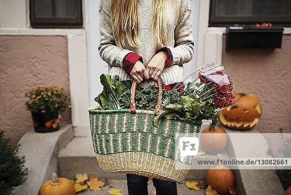 Mittelteil einer Frau  die eine Einkaufstasche mit Lebensmitteln hält