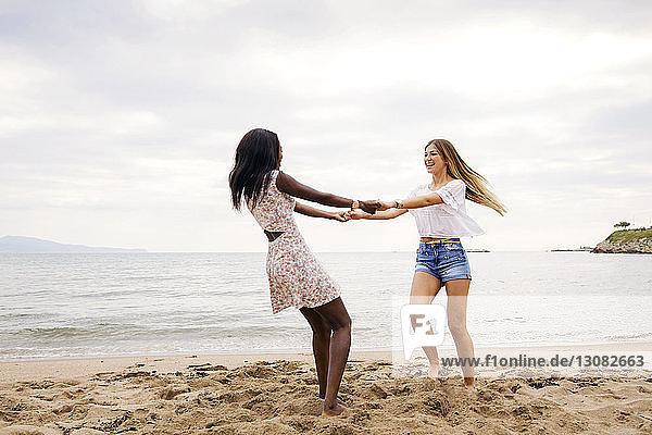Fröhliche Freundinnen spielen Ring-um-den-Rosen am Strand