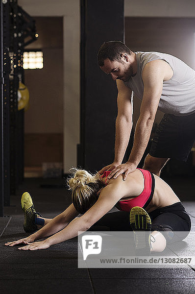 Male athlete assisting woman in stretching at gym