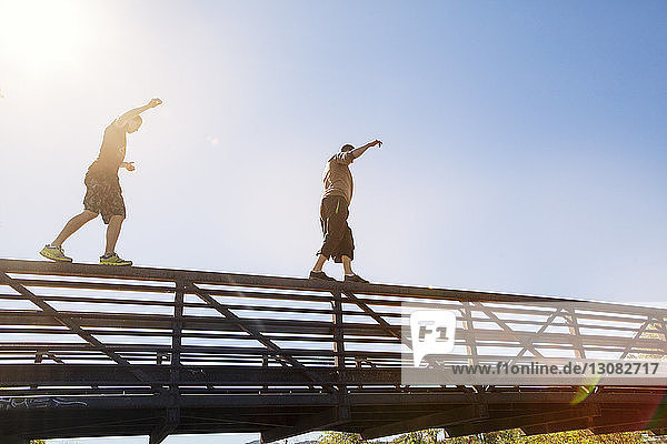 Low angle view of friends walking on bridge railing against clear blue sky