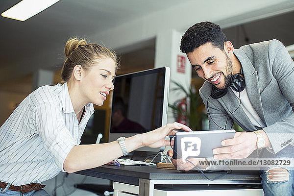 Kollegen mit Tablet-Computer am Tisch im Büro