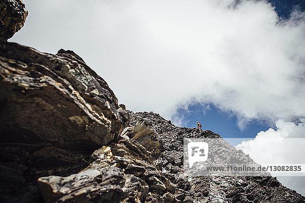 Mitteldistanzansicht eines Wanderers  der am sonnigen Tag den Berg gegen einen bewölkten Himmel besteigt
