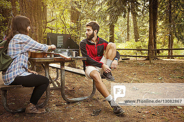 Friends talking while sitting at picnic table in forest