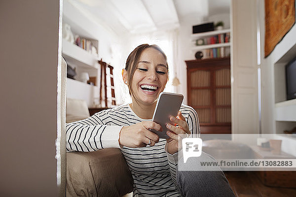 Happy woman text messaging while sitting at home