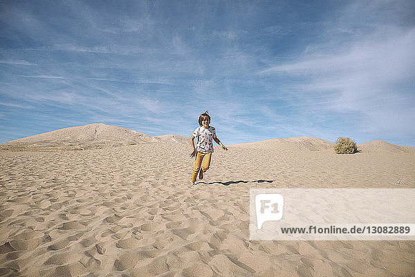 Playful boy running against cloudy sky at desert during sunny day