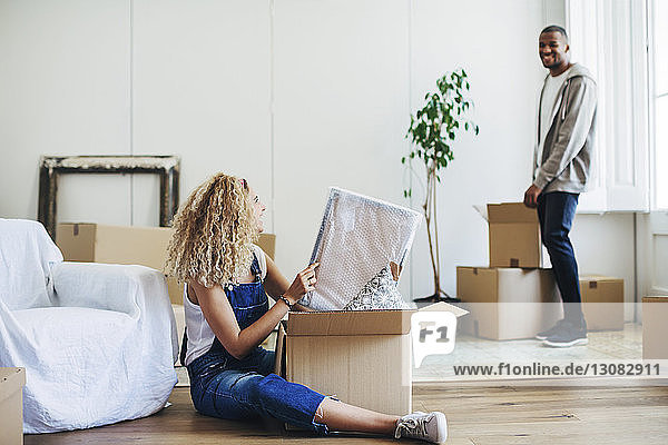 Couple unpacking boxes at new house