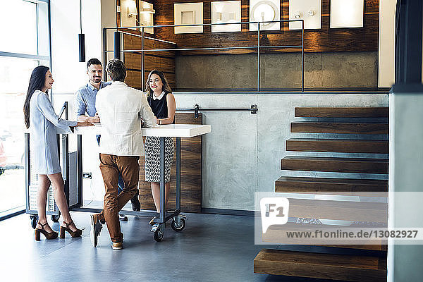 Happy business people discussing while standing by desk in office