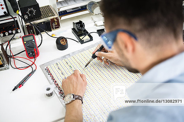 High angle view of engineer soldering circuit at table in electronics industry