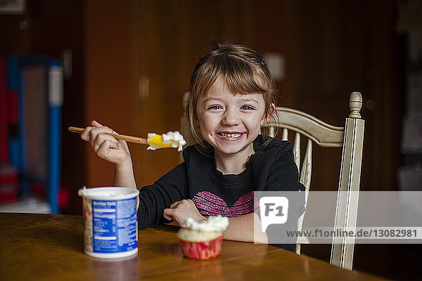 Portrait of happy girl eating cupcake at home