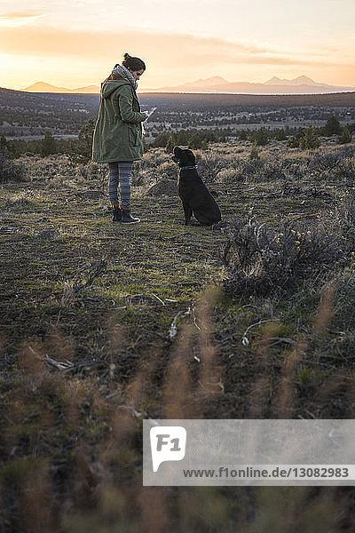 Frau in voller Länge  die bei Sonnenuntergang mit dem Hund auf dem Feld gegen den Himmel steht