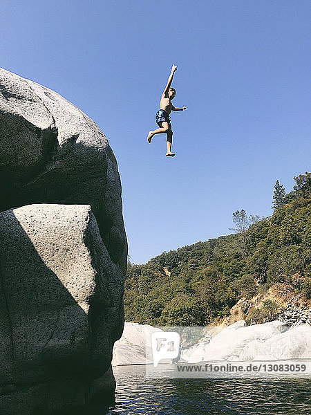 Low angle view of carefree shirtless boy jumping in Yuba River from cliff