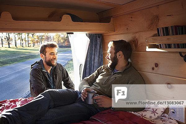 Mann unterhält sich mit Freund  der sich im Wohnmobil entspannt