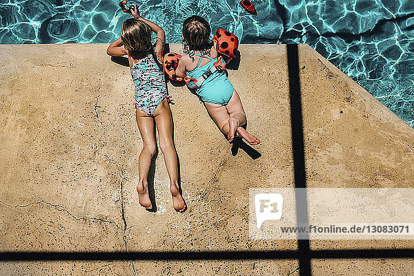 High angle view of sisters lying at poolside during sunny day