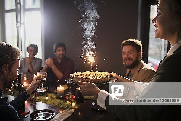 Frau serviert Freunden zu Weihnachten Torte mit angezündeter Kerze