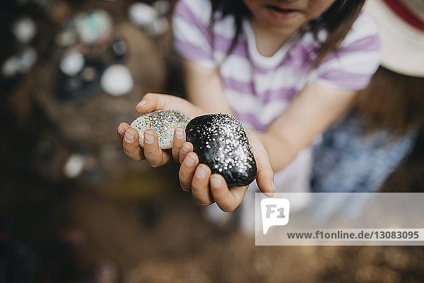 Midsection of girl showing decorated rocks with glitter