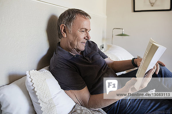 Senior man reading book while sitting on bed at home