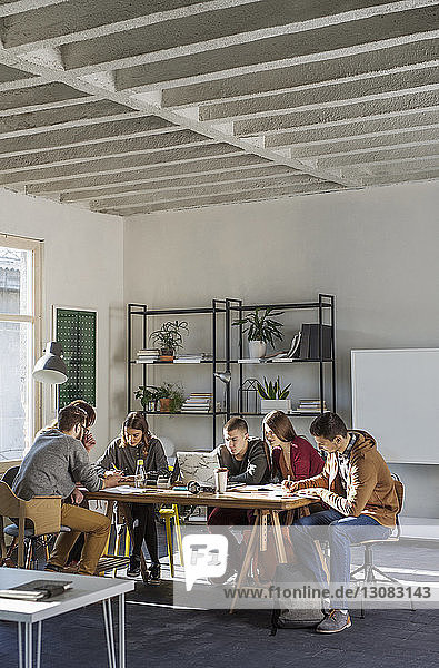Students studying at table by window in classroom