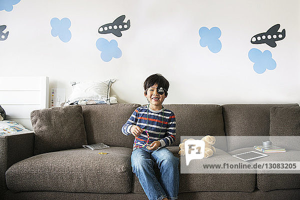 Happy boy playing with toys on sofa at home