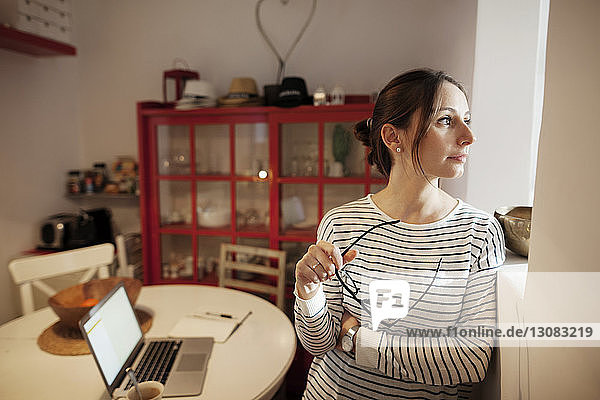 Thoughtful woman holding eyeglasses while leaning on wall at home