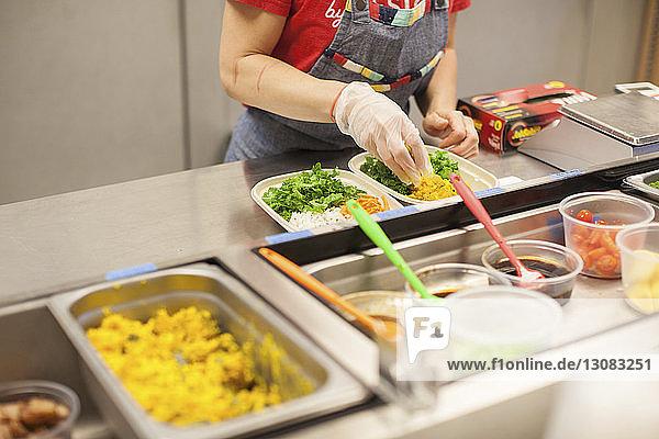 Mitschnitt eines weiblichen Kochs  der Essen in einem Teller auf der Küchentheke eines Restaurants serviert