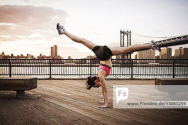 Frau macht Spagat im Handstand auf der Promenade gegen die Manhattan-Brücke