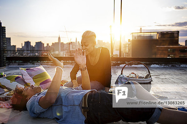 Man lying besides woman sitting on rooftop against sky during sunset