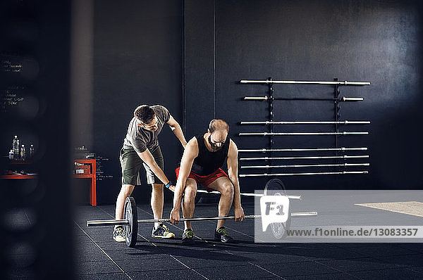 Trainer assisting male athlete in lifting barbell at gym