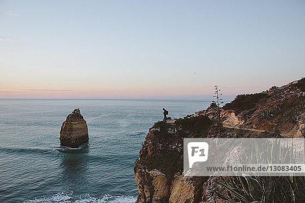 Mitteldistanzansicht eines auf einer Klippe am Meer stehenden Silhouettenmannes gegen den Himmel
