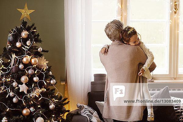 Rückansicht einer Großmutter  die zu Weihnachten ihre Enkelin zu Hause trägt