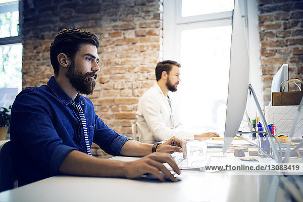 Young businessmen using computer at desk in creative office