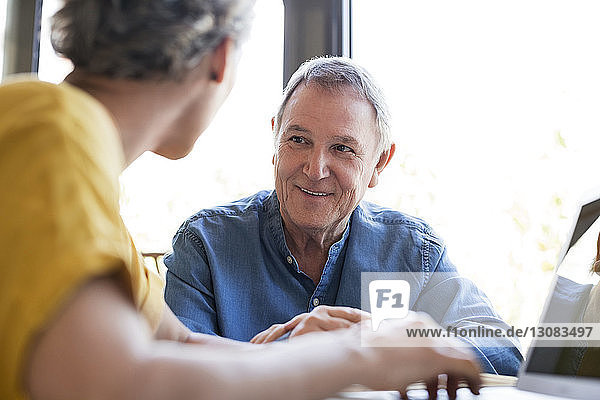 Glücklicher älterer Mann plant Urlaub mit Frau zu Hause