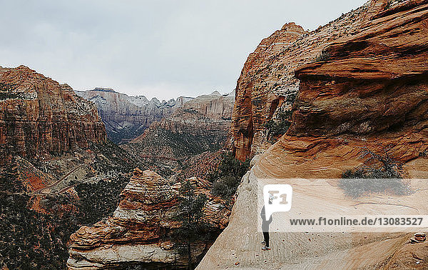 Full length of female hiker standing on rock formation at Zion National Park