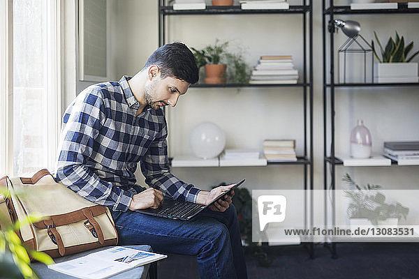 Mann benutzt Laptop-Computer  während er auf einem Sitz im Klassenzimmer sitzt