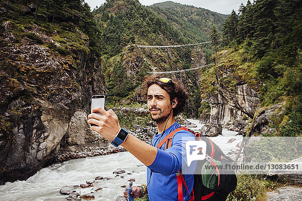 Hiker with backpack taking selfie while standing by river at Sagarmatha National Park