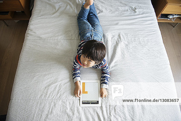 High angle view of smiling boy using digital tablet on bed