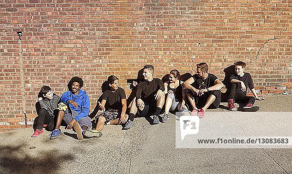 Happy friends talking while relaxing against brick wall on sunny day