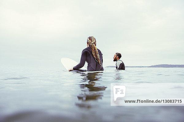 Männliche und weibliche Surfer entspannen sich im Meer vor bewölktem Himmel