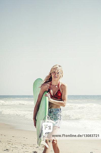 Porträt einer selbstbewussten Frau  die beim Strandspaziergang ein Surfbrett trägt