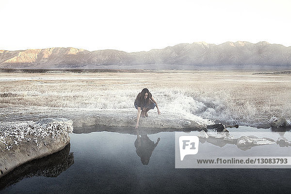 Woman touching water at Mammoth Lake Hot Springs against mountains
