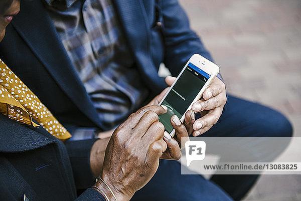 Mittelteil eines Paares  das ein Mobiltelefon benutzt  während es in der Stadt sitzt