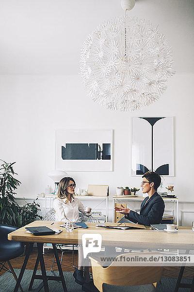 Geschäftsfrauen diskutieren  während sie im Büro am Tisch sitzen