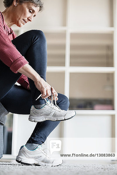 Side view of mature woman wearing sports shoe at home