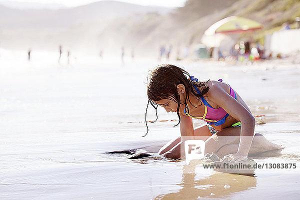 Mädchen spielt auf nassem Sand am Ufer